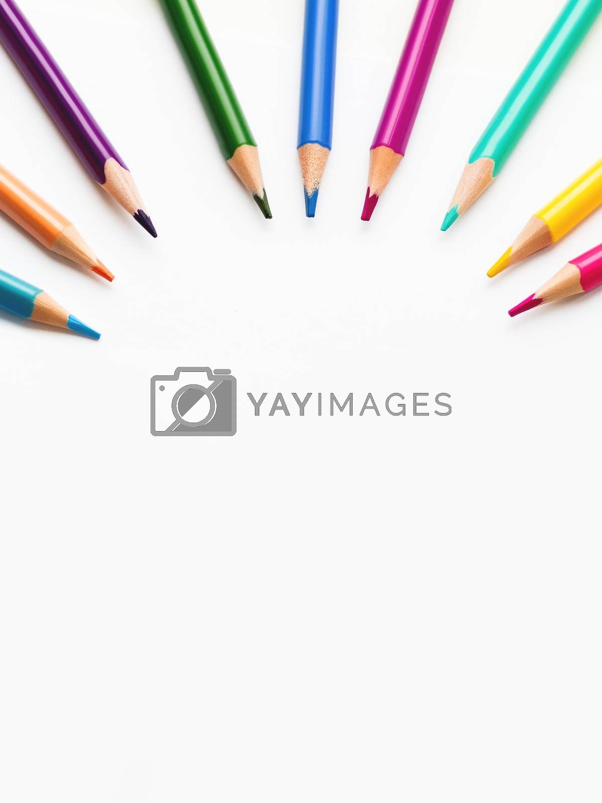 Colorful watercolor pencils on white background. School supplies with round copy space. Kid's stationery. Back to school circle backdrop.
