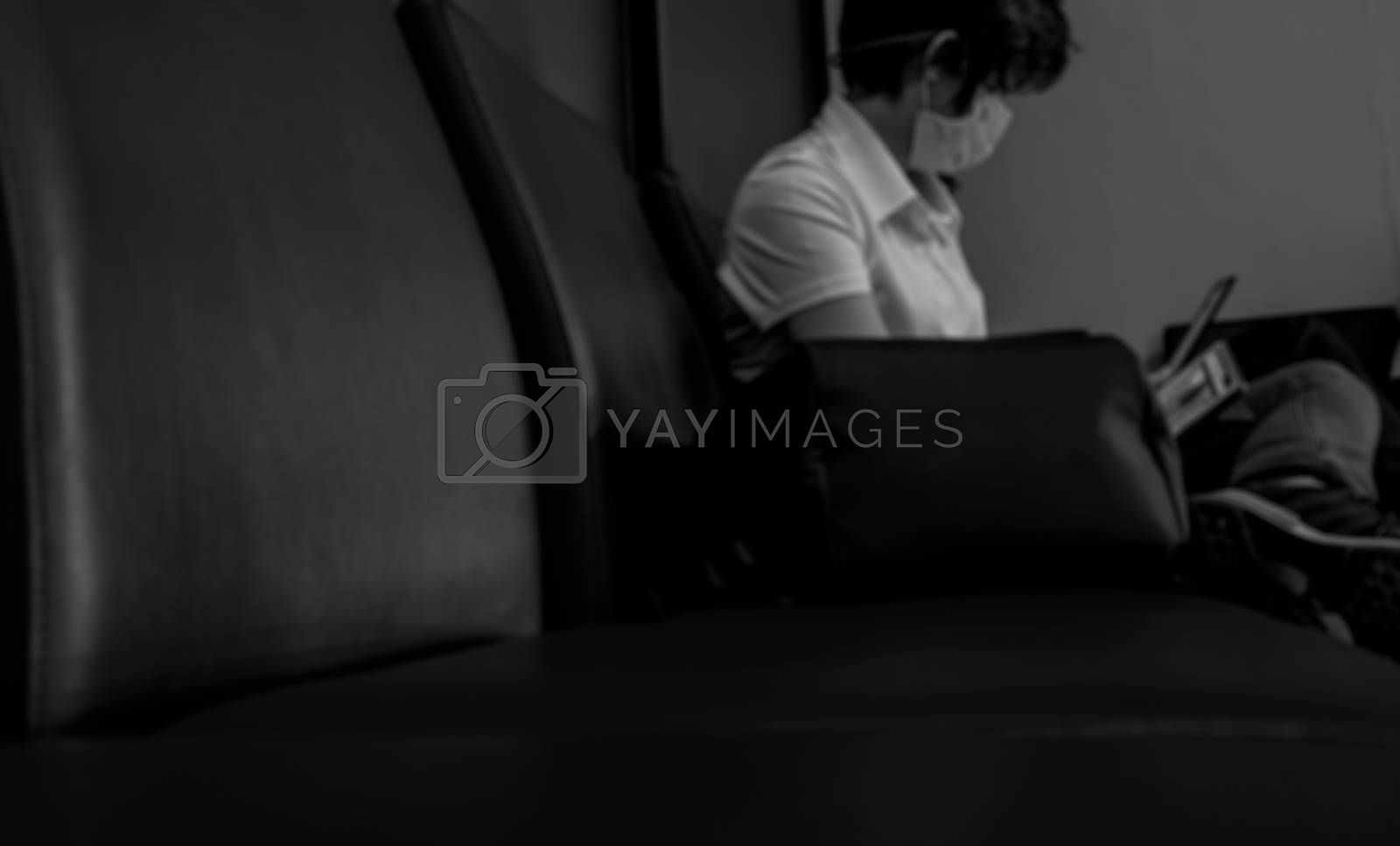 Blurred woman wear surgical mask and sit on seat using laptop for work in public place waiting for train or airplane flight. Social distancing concept. Coronavirus impact on people lifestyle.