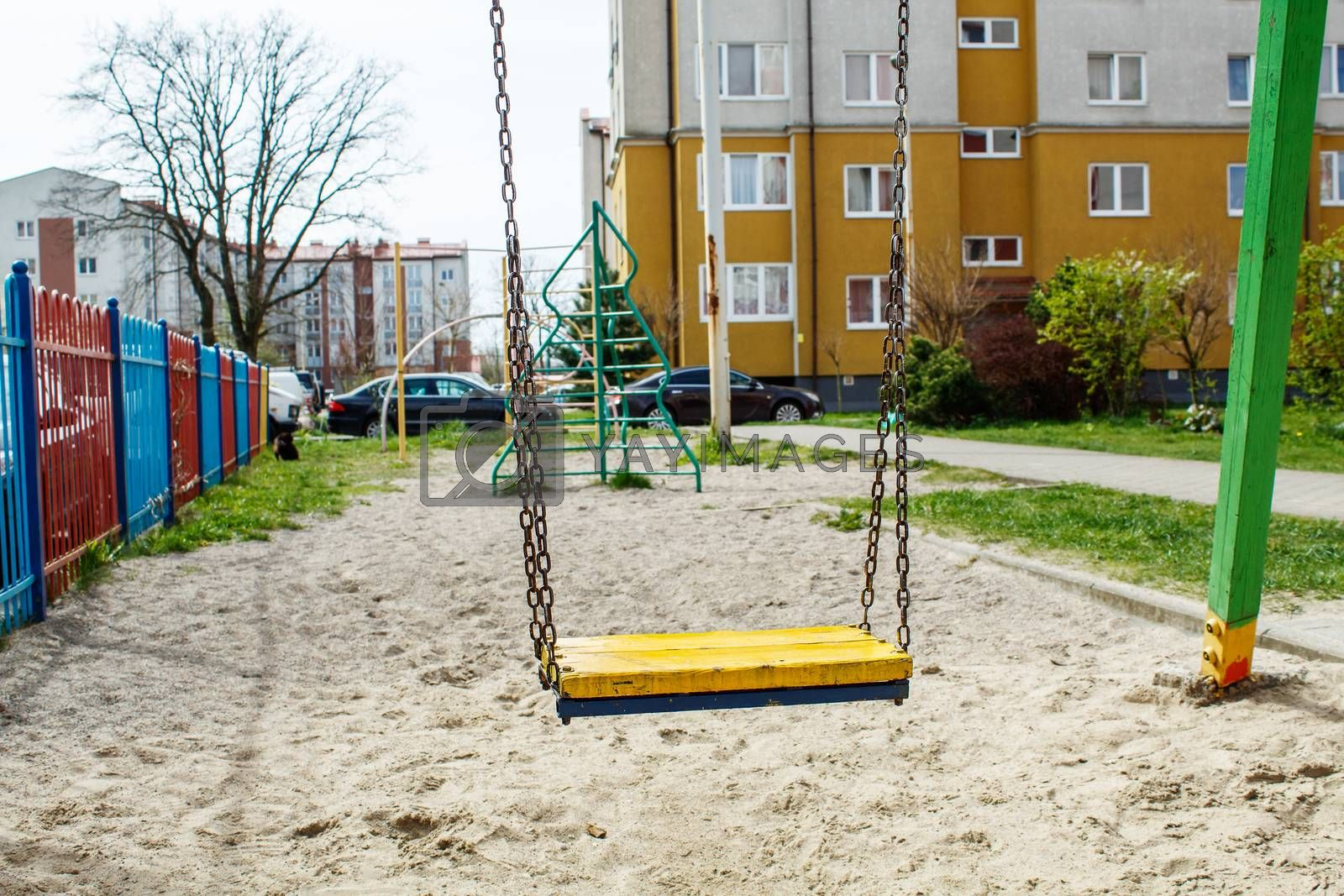 empty swing on quarantined playground on sunny spring day