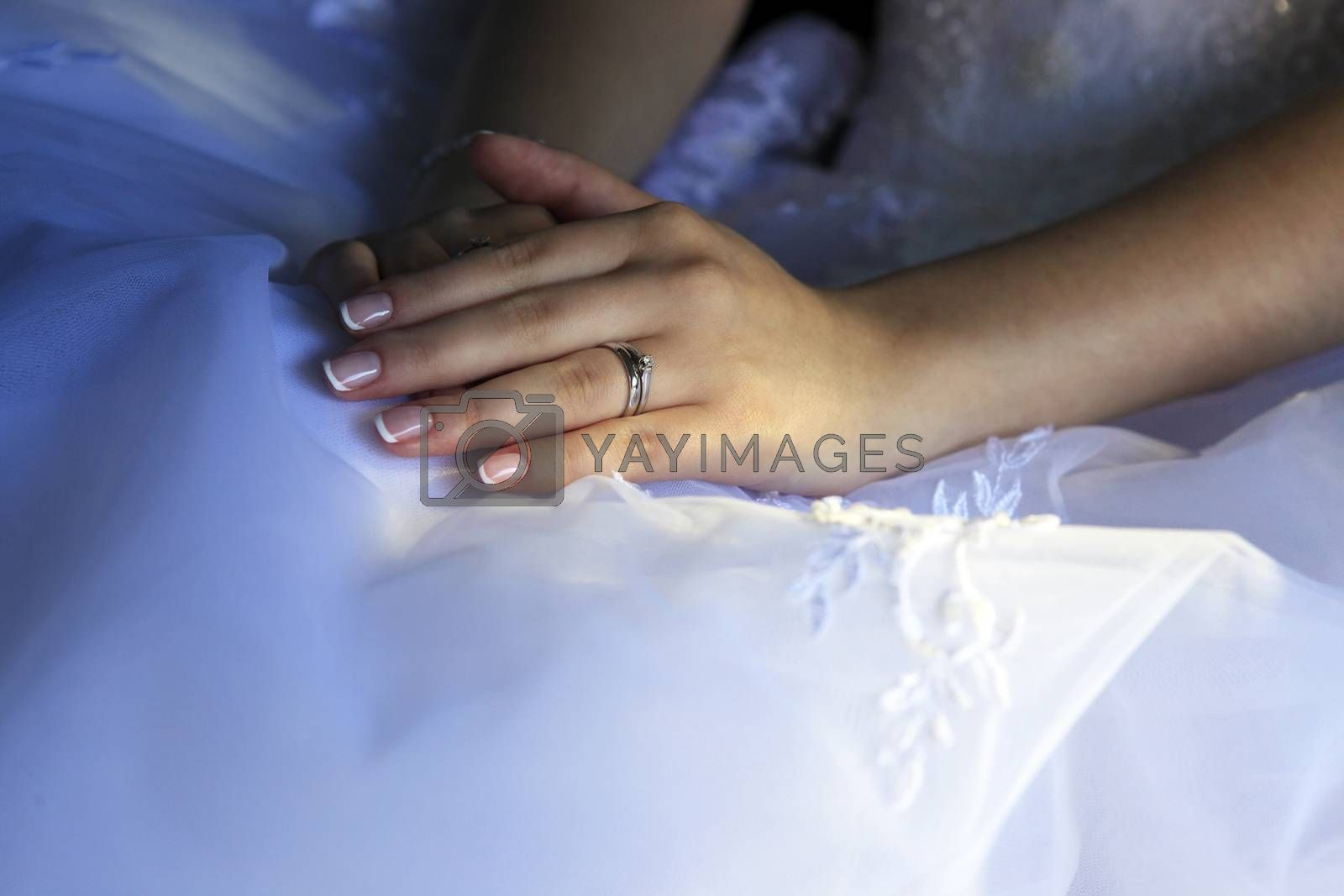 Hands of the bride on a background of a wedding dress.