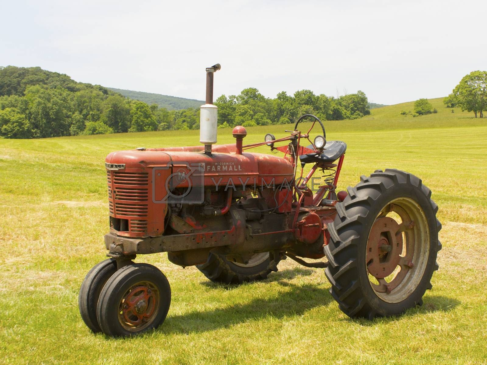 Old McCormick Farmall tractor sitting in a field