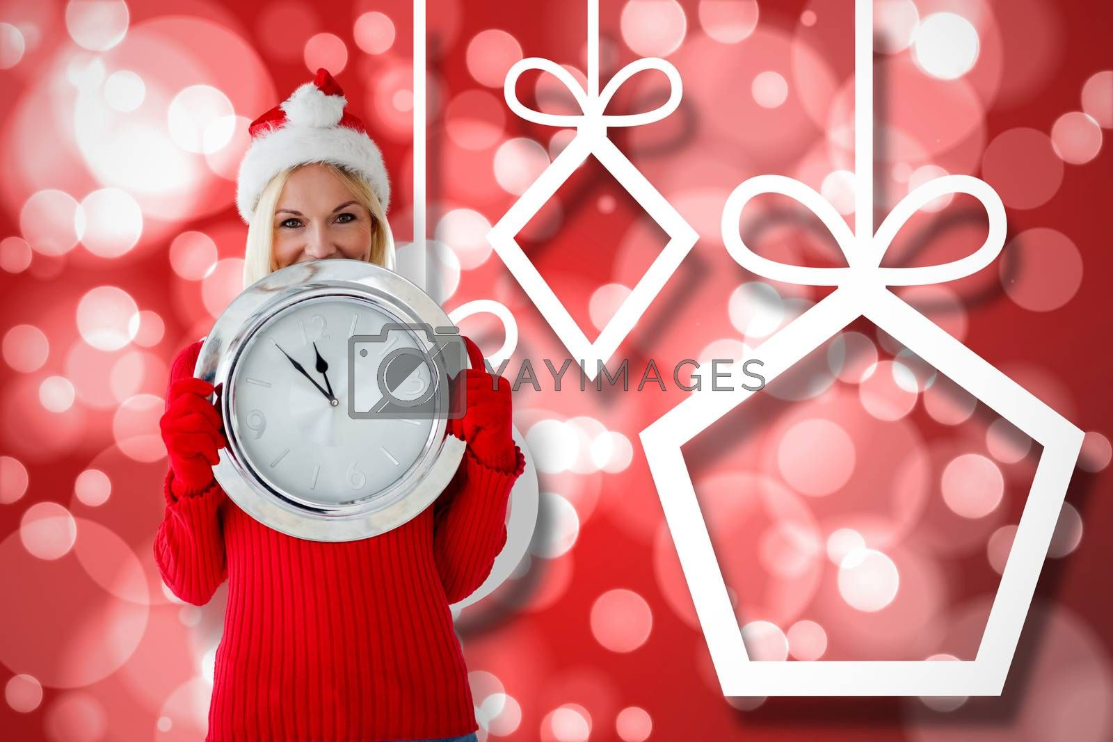 Happy festive blonde with clock against hanging christmas decorations on lights