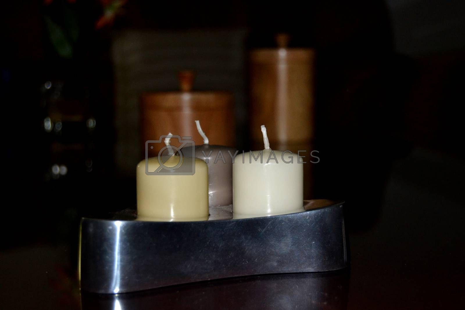 Silver candleholder containing three coloured candles in brown tones
