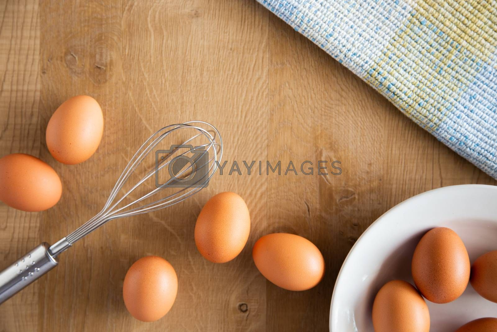 Chicken eggs and egg beater on wooden background.