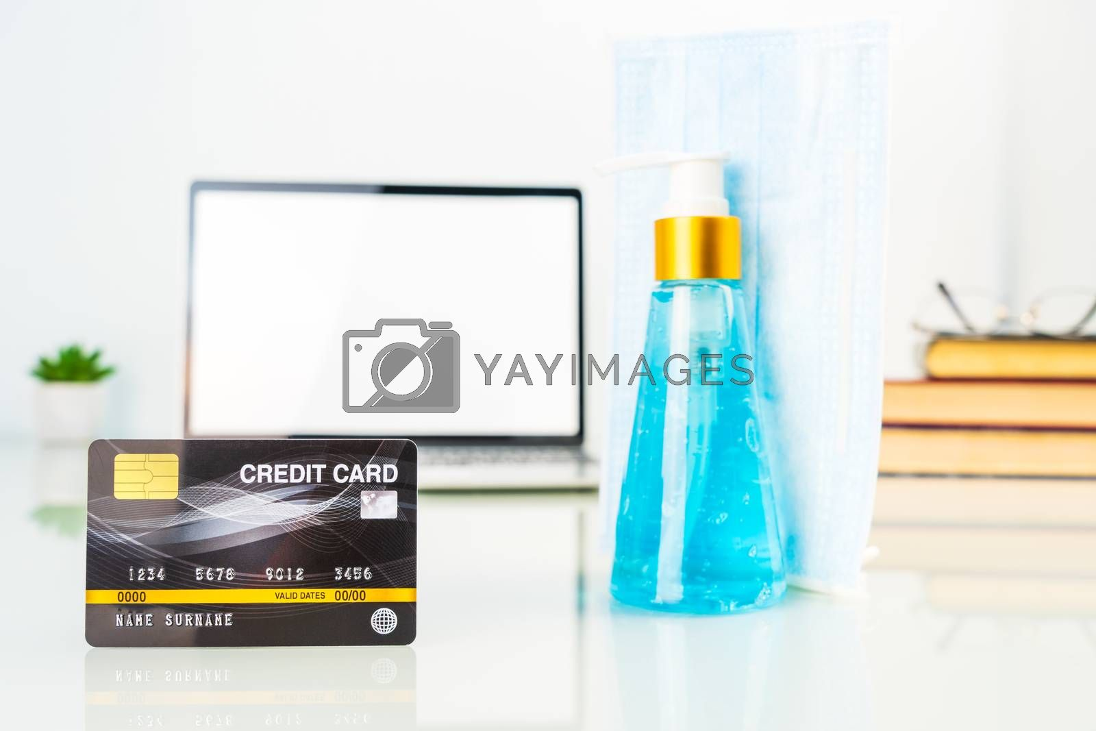 Online shopping, credit card front of laptop screen with hand sanitizer and surgical mask, Quarantine work from home concept against covid-19 epidemic
