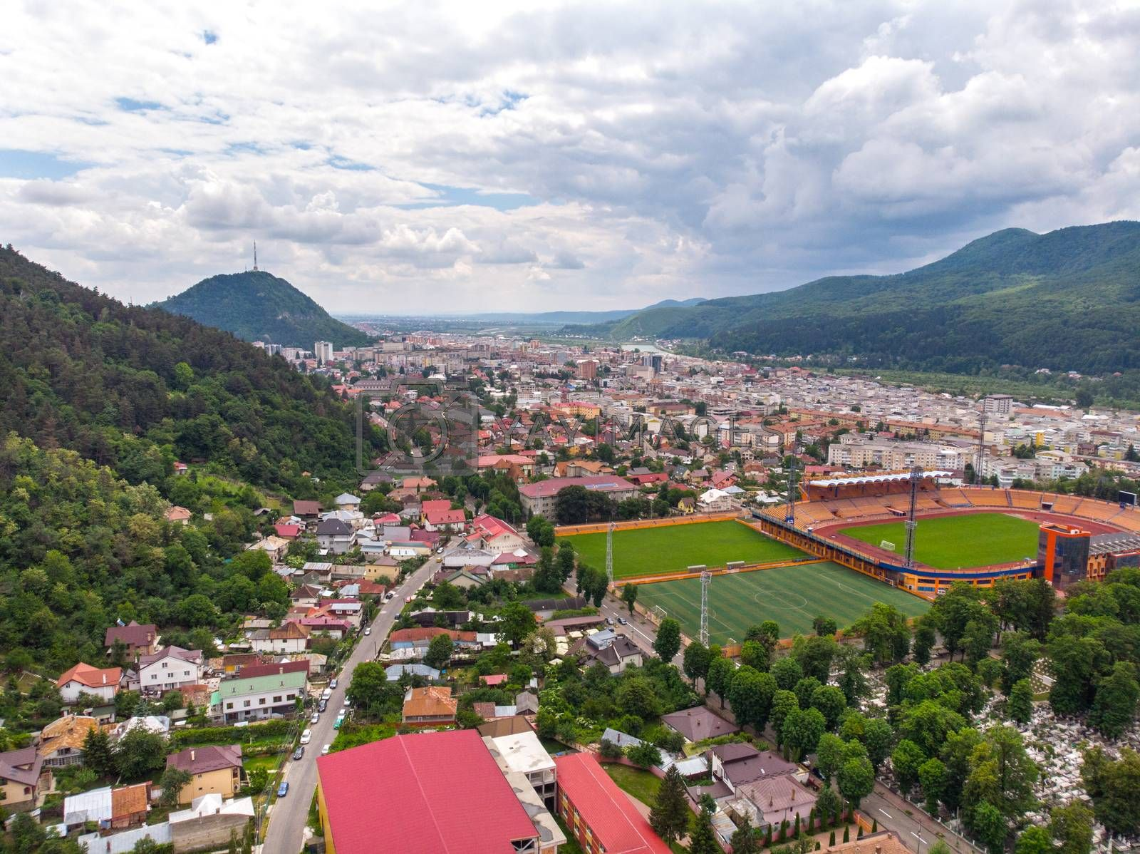 Aerial mountain city view with a small football stadium in front. Piatra Neamt aerial view in Romania