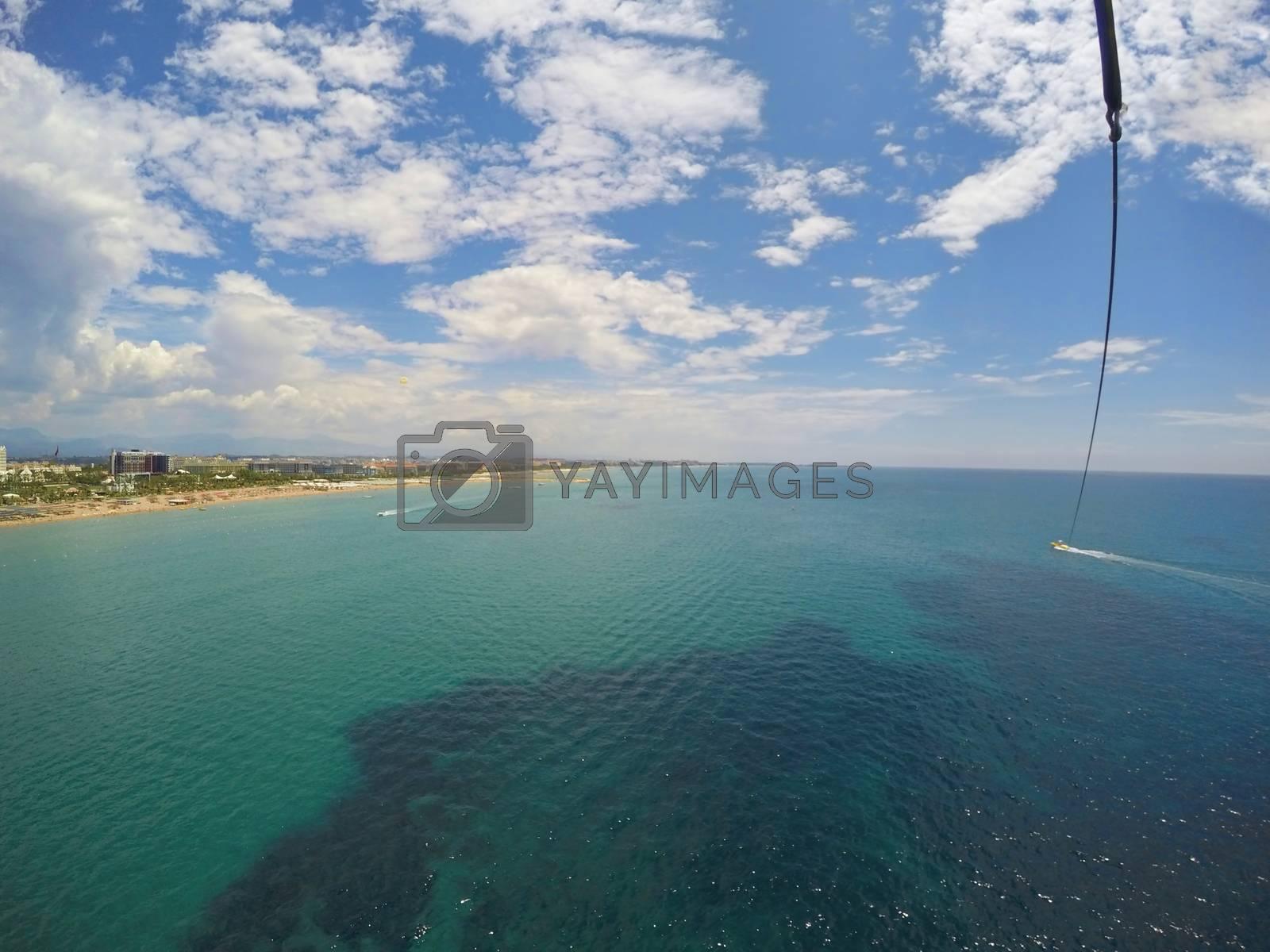 Aerial view of tropical resort during parasailing (speedboat dragging parachute), mediterranean beach in Turkey
