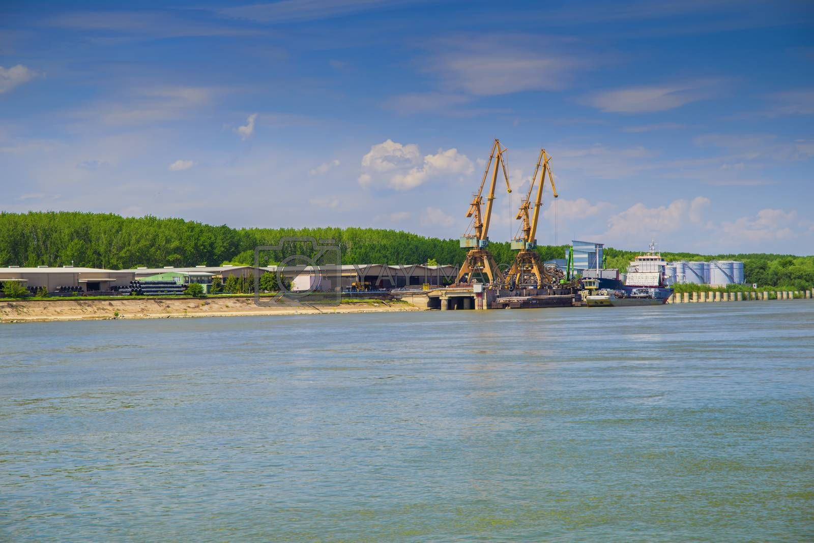 Shipyard with cranes on Danube river in a sunny summer day