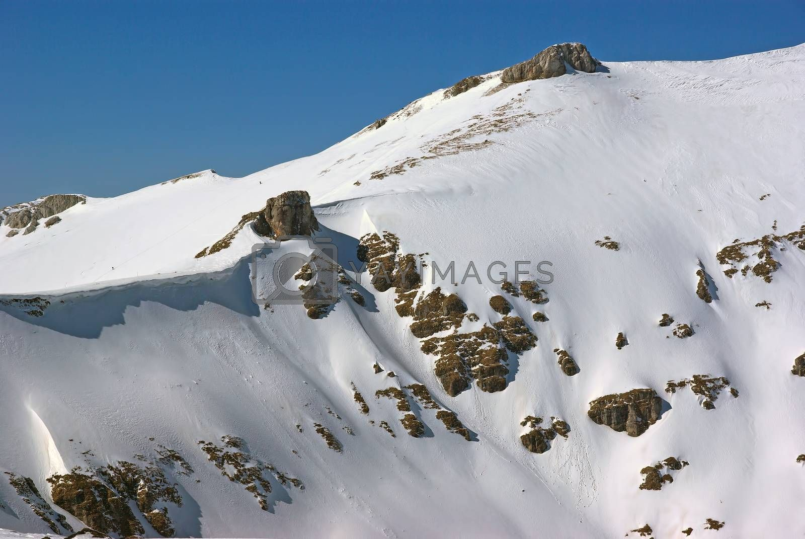 Snow covering the rocky mountain in Romanian Carpathians, winter landscape in a beautiful day
