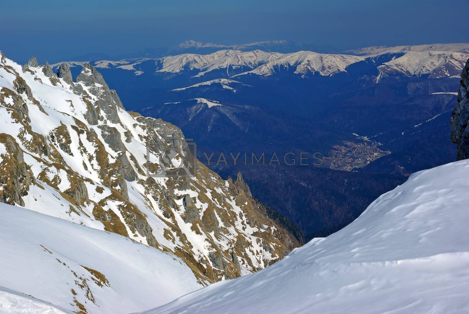 Winter mountain scene: snow covered rocks and sports resort to the valley
