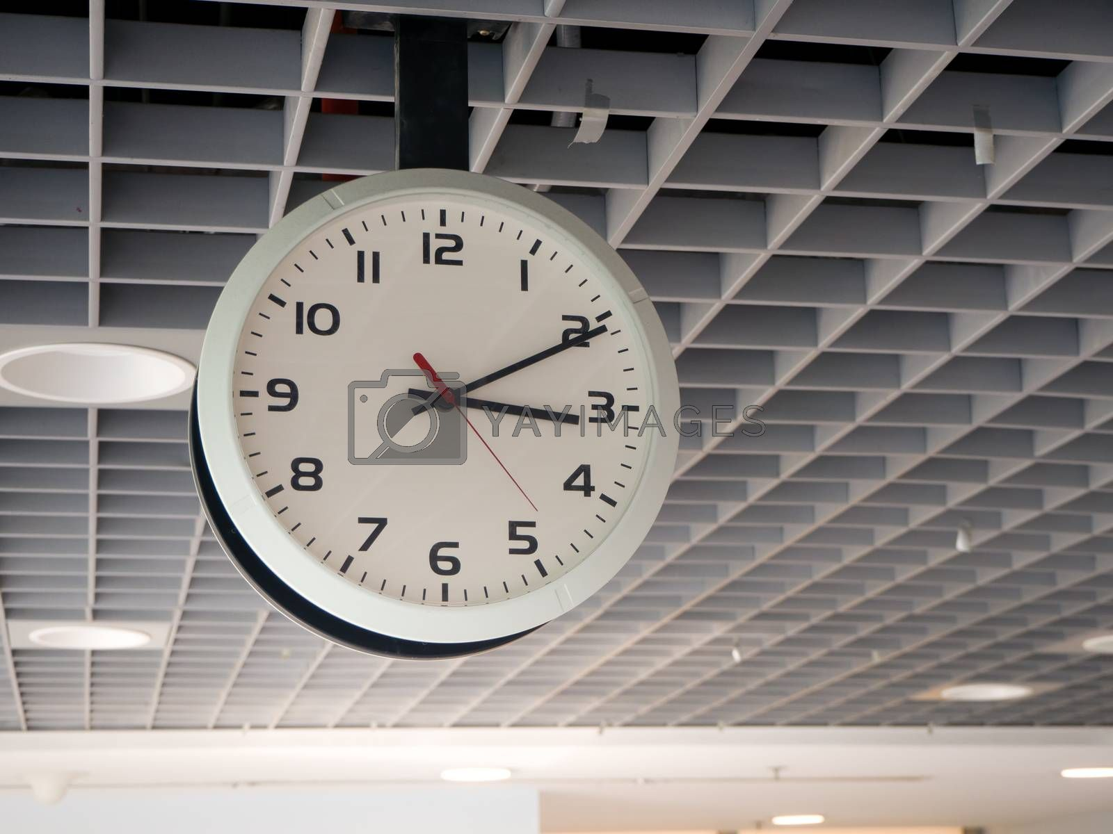 train station clock hanging from the ceiling.