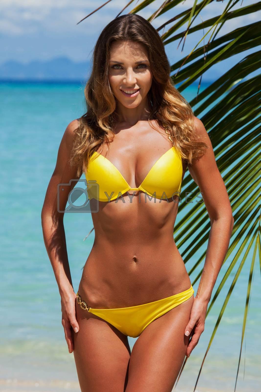 Young female in yellow bikini enjoying sunny day under palm tree on the tropical beach