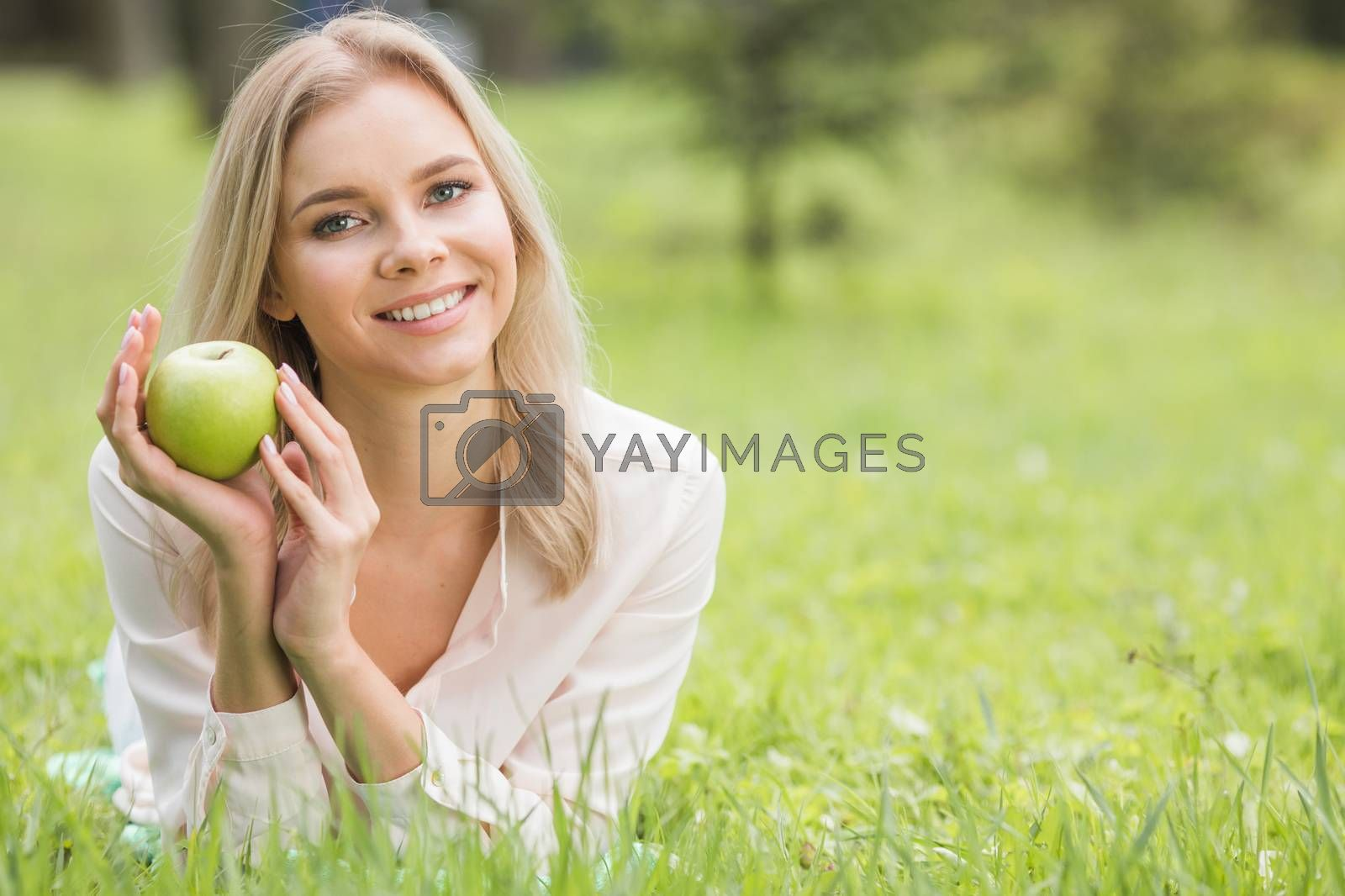 Woman with apple on grass by Yellowj