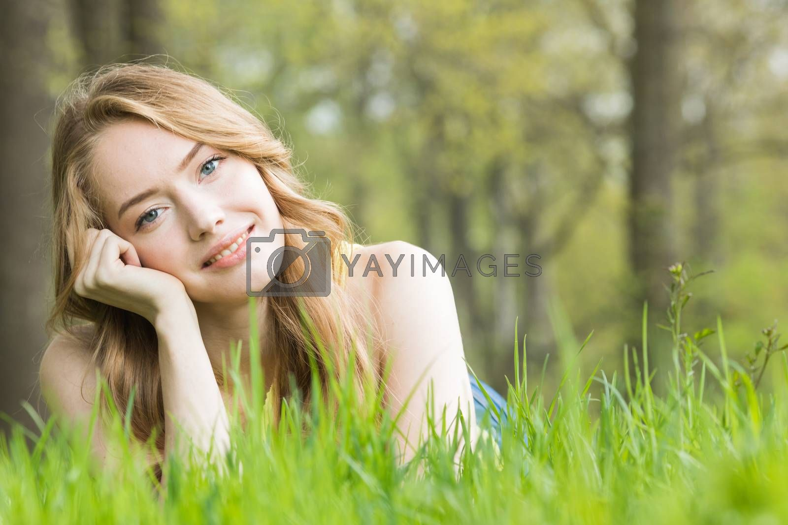Happy smiling young woman laying on the green grass