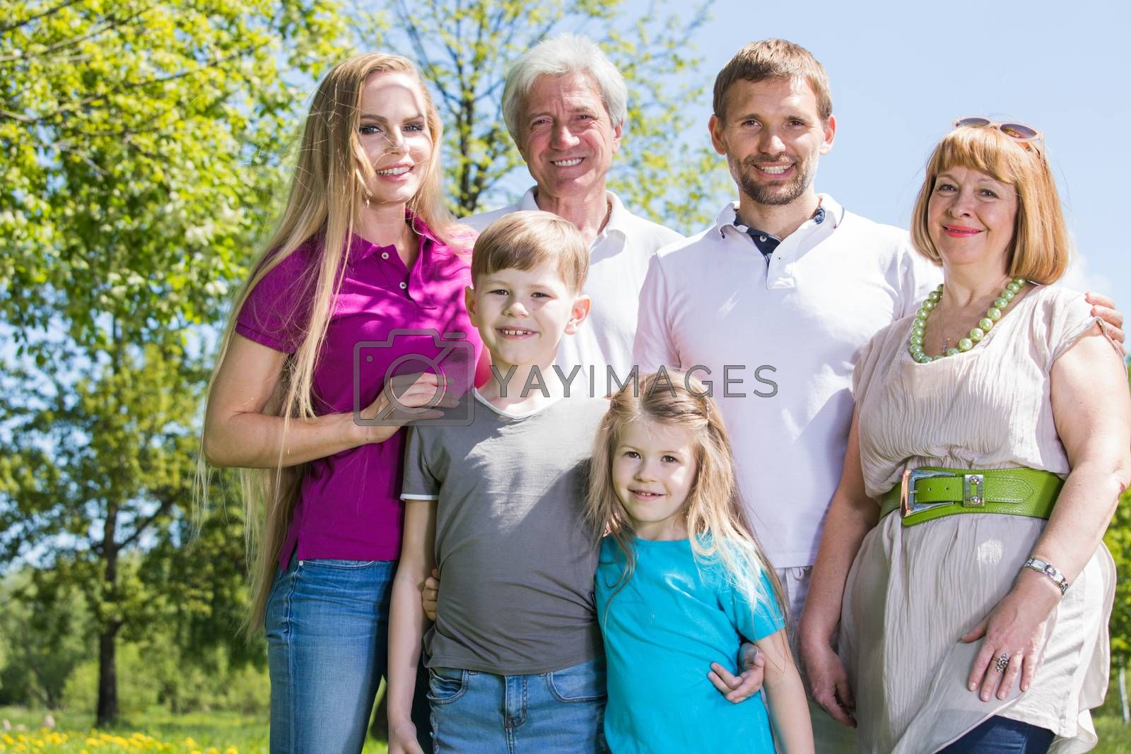 Multigeneration family portrait outdoors. Happy parents with two children and grandparents in summer park