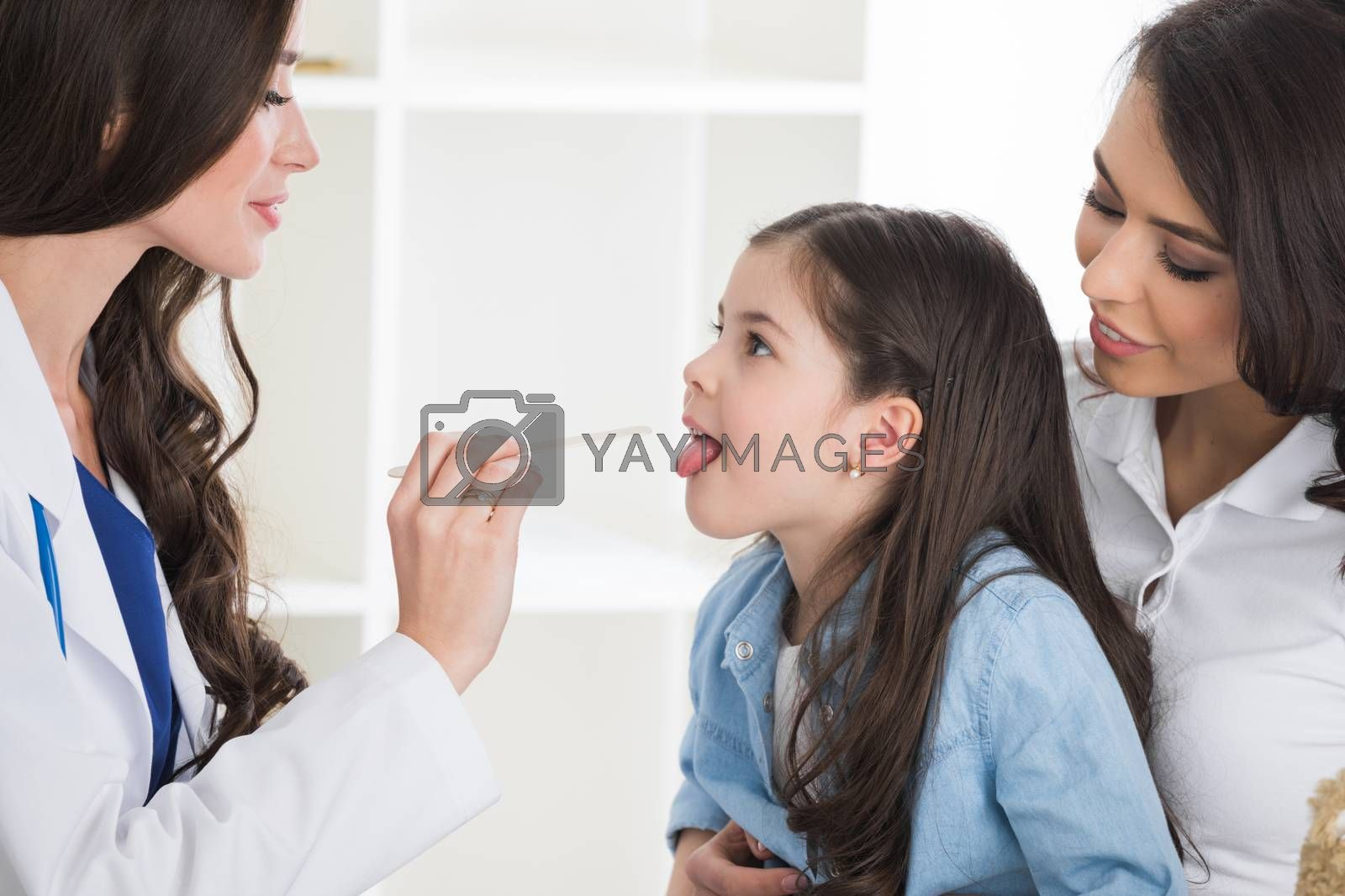 Little girl having throat examination by pediatrician at checkup in clinic