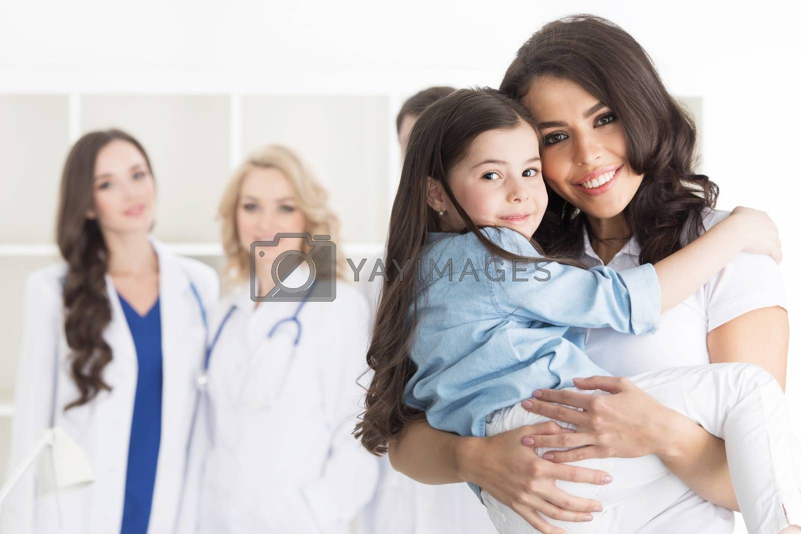 Mother and daughter in medical clinic, team of doctors on background