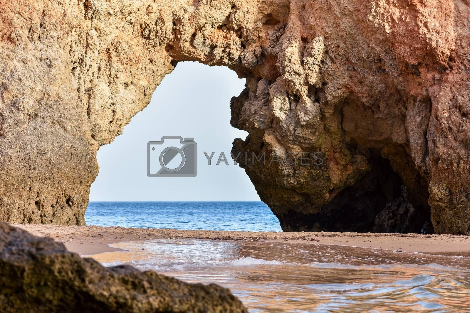 Empty beach between cliffs and natural archway through which you can see the sea. Uncrowded travel concept. Algarve, Portugal. Algarve, Portugal