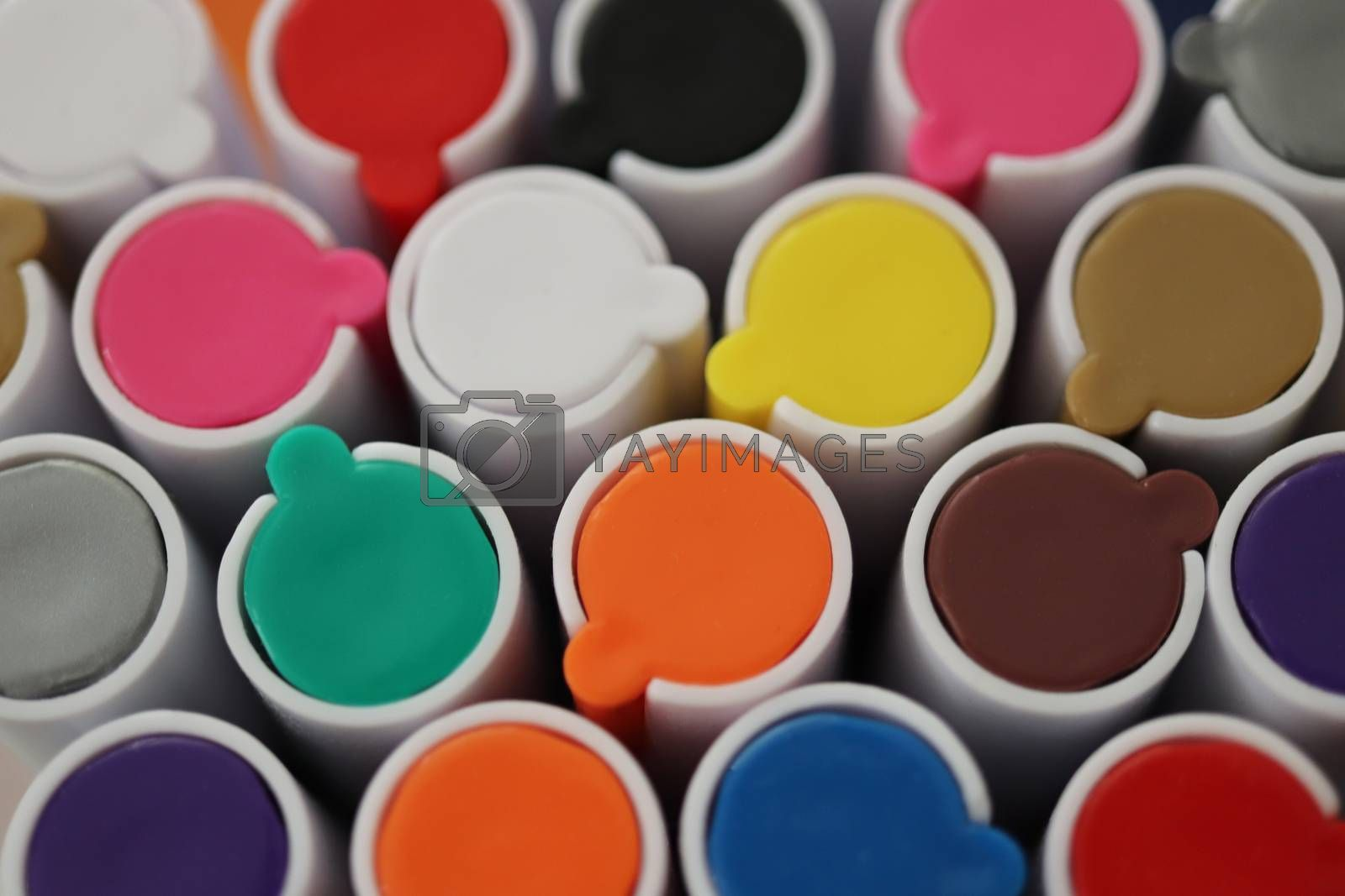 Back to school composition. Colored market caps background. Pen markers multicolor caps macro closeup.