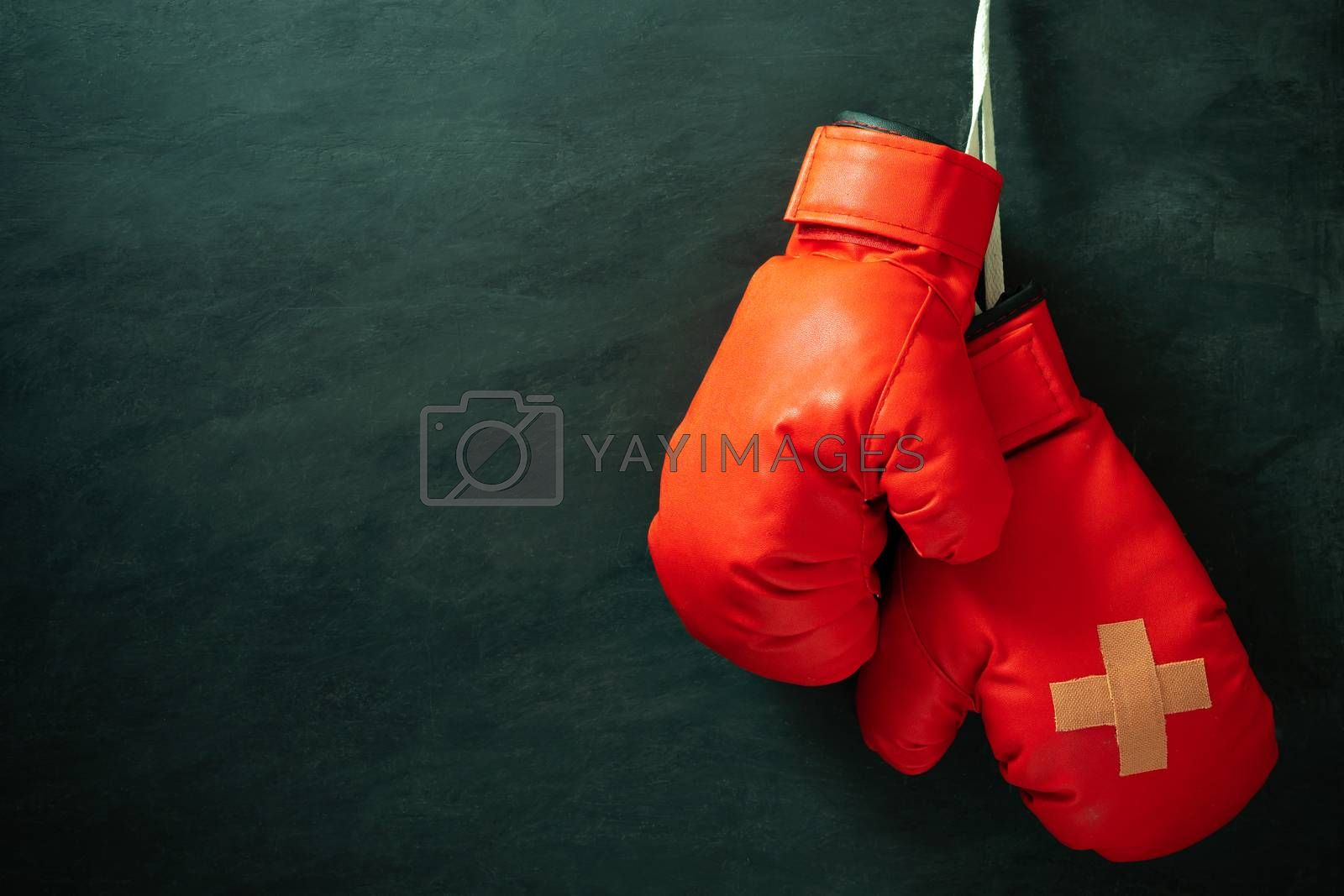 Red boxing gloves hung on black cement wall in darkness with lighting. Adhesive plaster across each other on boxing gloves. Idea of hurt or combat losing business rivals. Fighting giving up boxing.