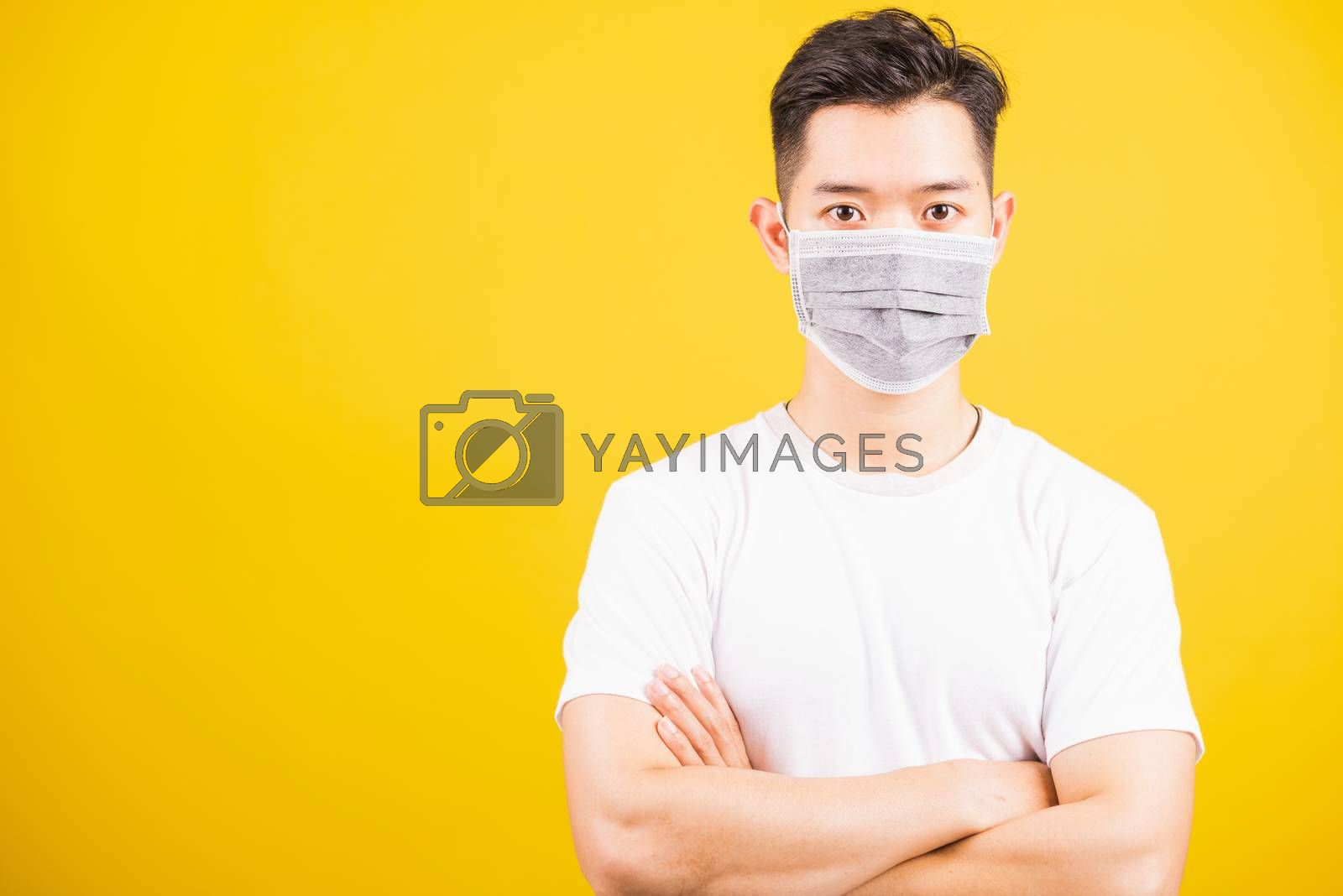 Closeup Asian young handsome man wearing face mask protective germ virus and stand crossed arm, studio shot isolated on yellow background and copy space, medical outbreak coronavirus COVID-19 concept