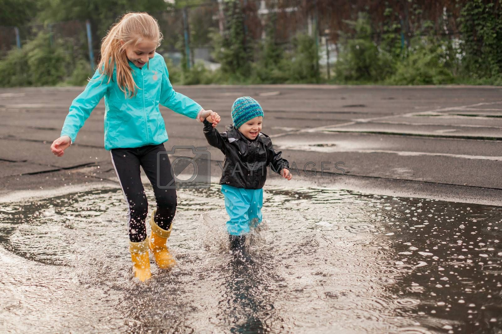 Royalty free image of Boy and girl jumping in puddle in waterproof coat and rubber boots by Angel_a
