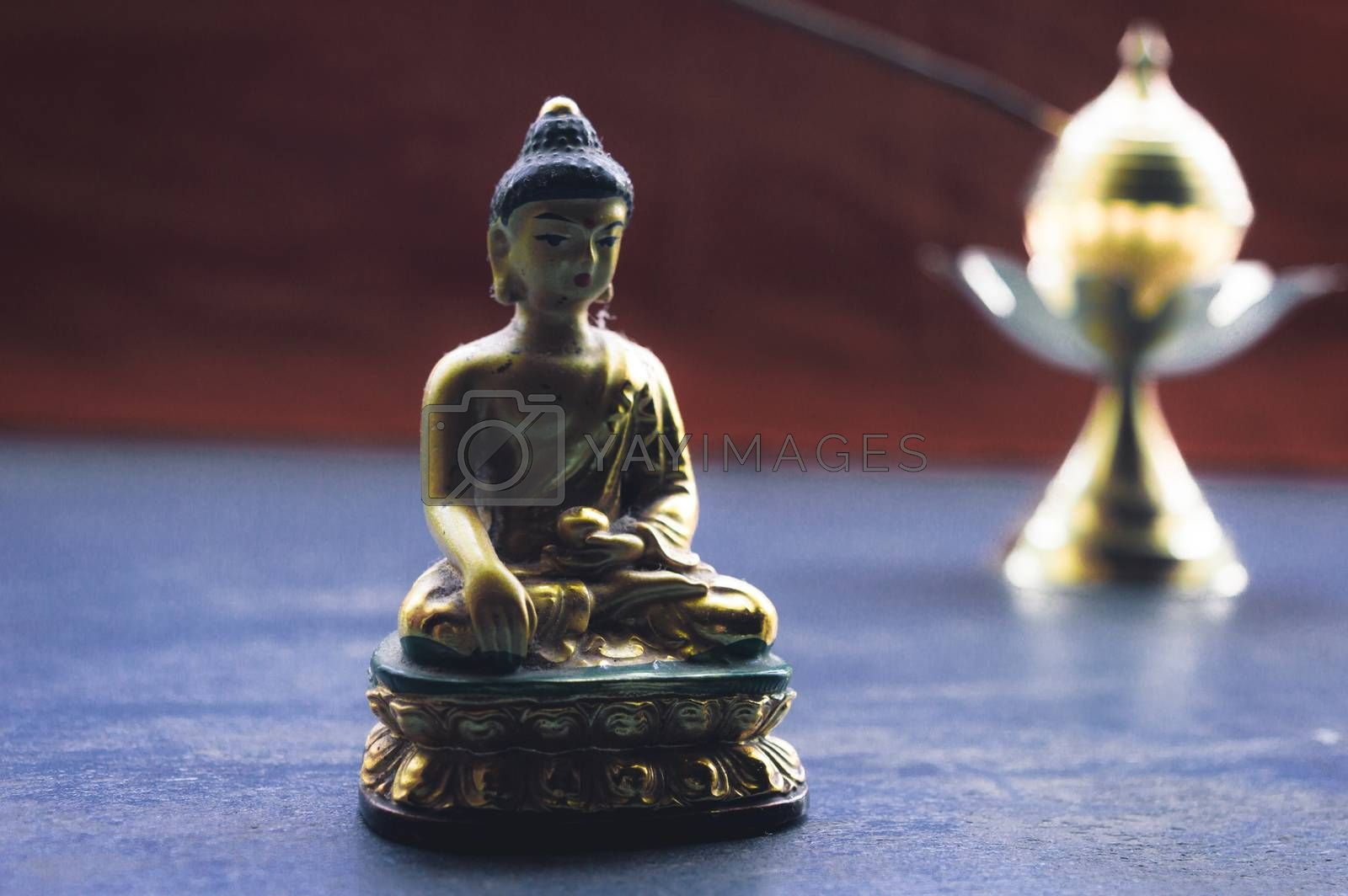 Close up Still Life of antique Meditating Buddha and bell on rustic floor. Faith, Tradition, Spirituality, Prayer, symbols of peace and Religious Themes. Arts and culture background concept. Copy space room for text for massage.