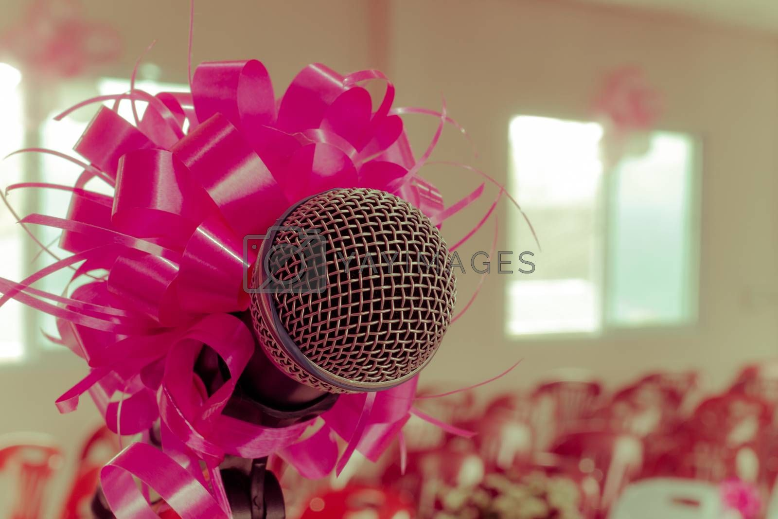microphone with pink bow and ribbon in wedding ceremony hall, vintage retro style.