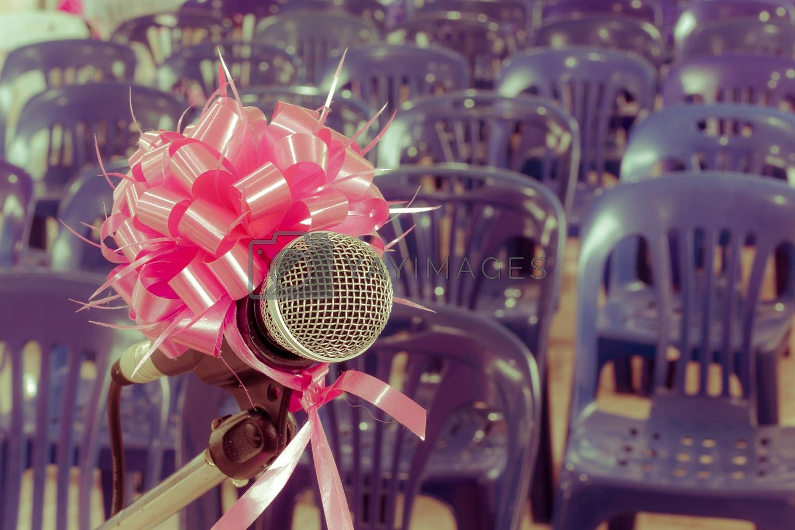 microphone with pink bow and ribbon in the background of blue chairs, retro vintage style.