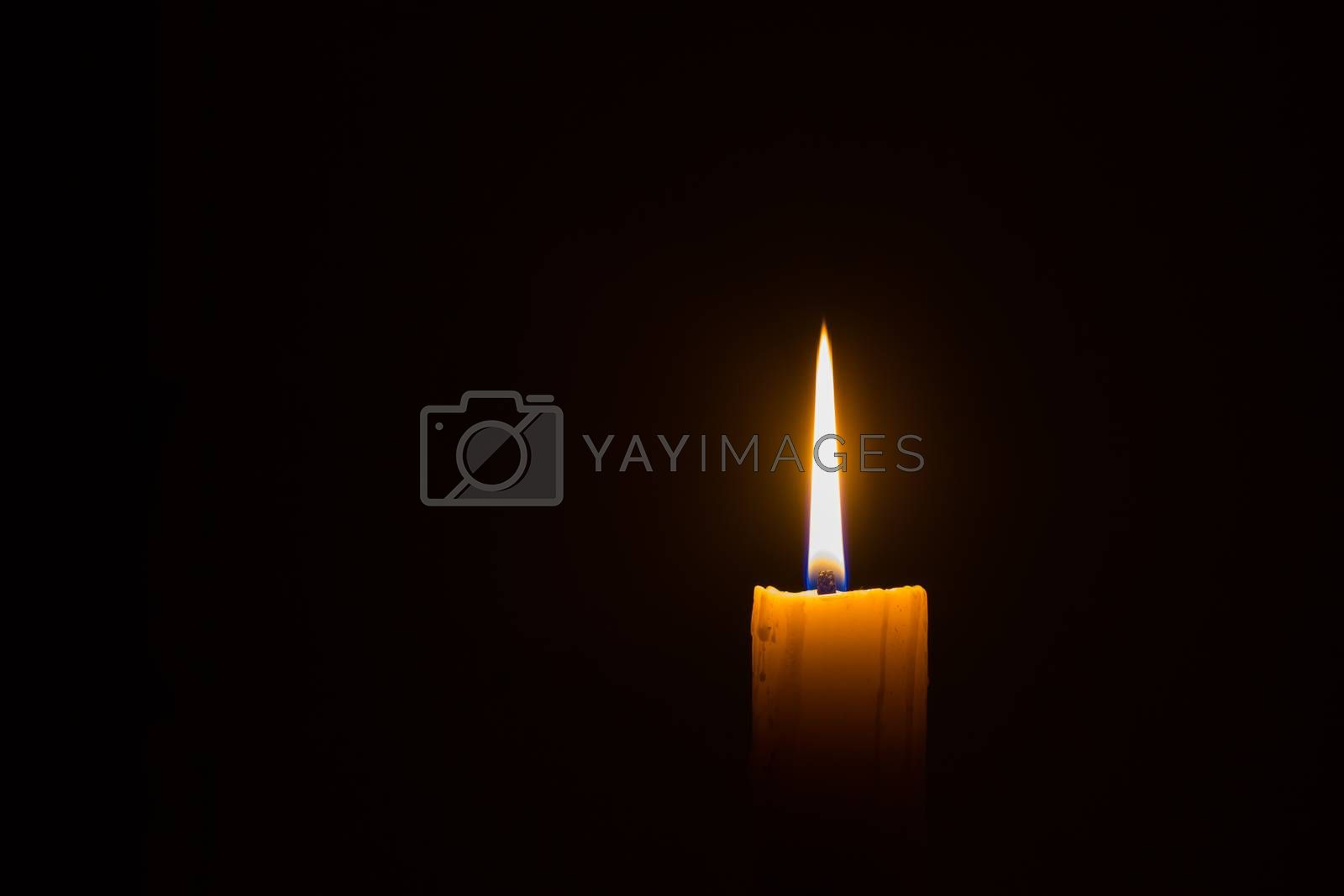 horizontal photo of candle on black background with copyspace