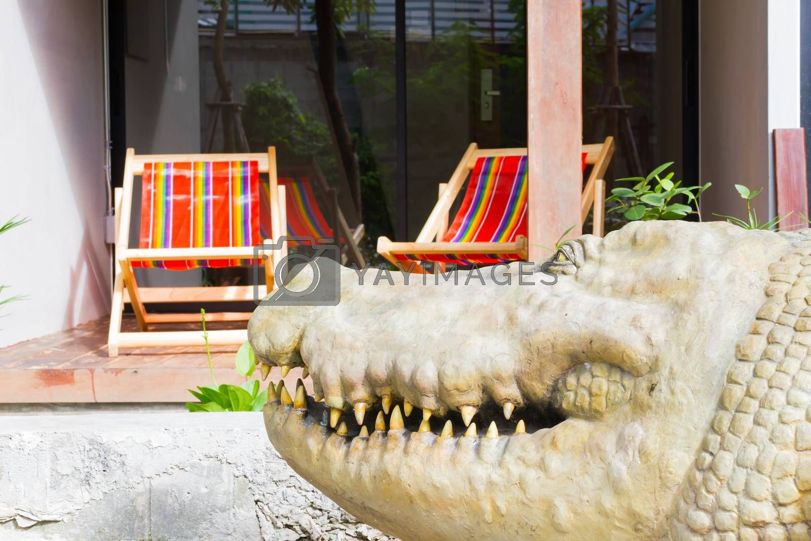 close-up crocodile on the blur background of beach chair in hotel
