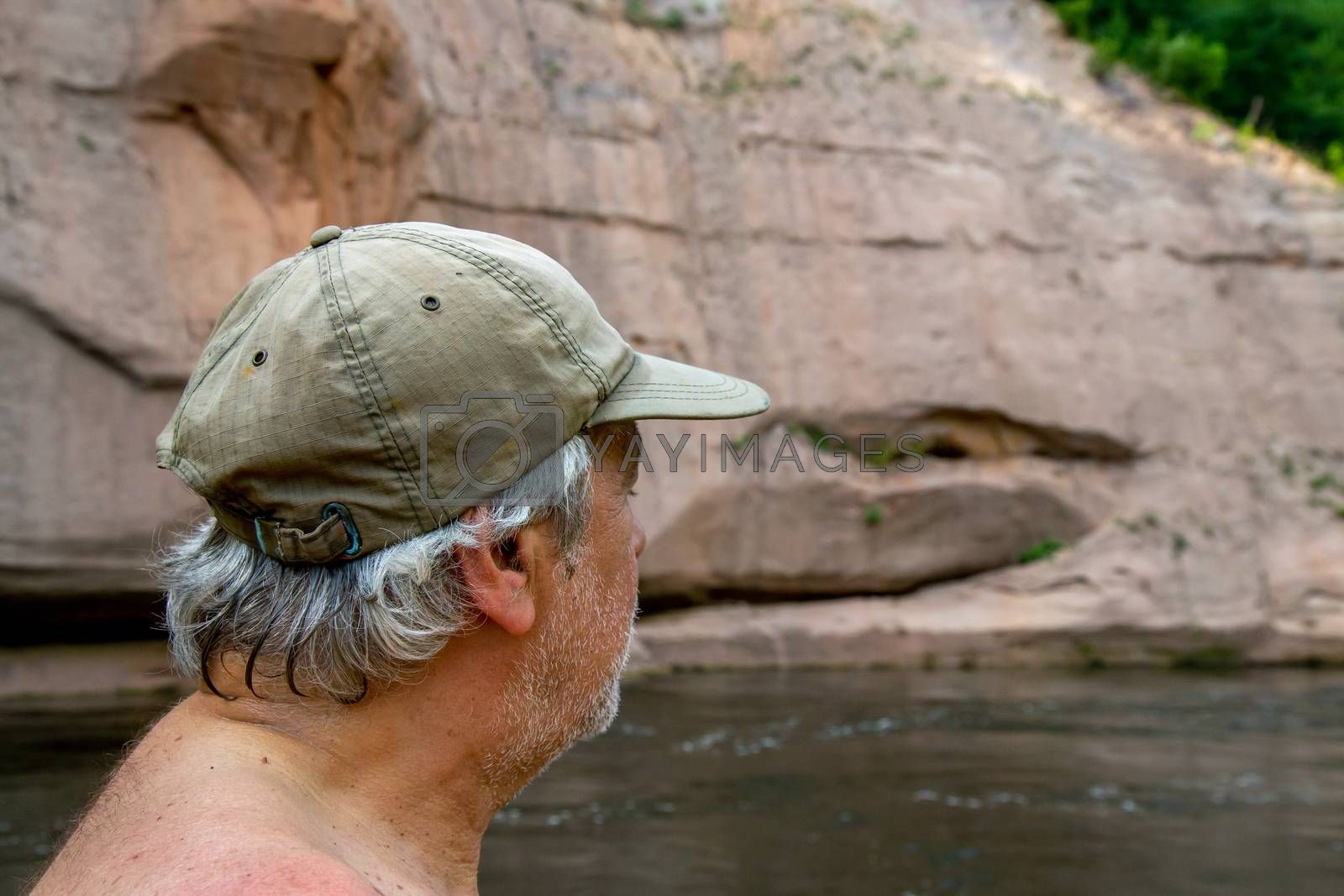 Man at the rock. Portrait of man at the rock,  on coast of the river. The man looks at the cliff. Rock on the Gauja river. Cliff is steep rock face, especially at the edge of the river or the sea.