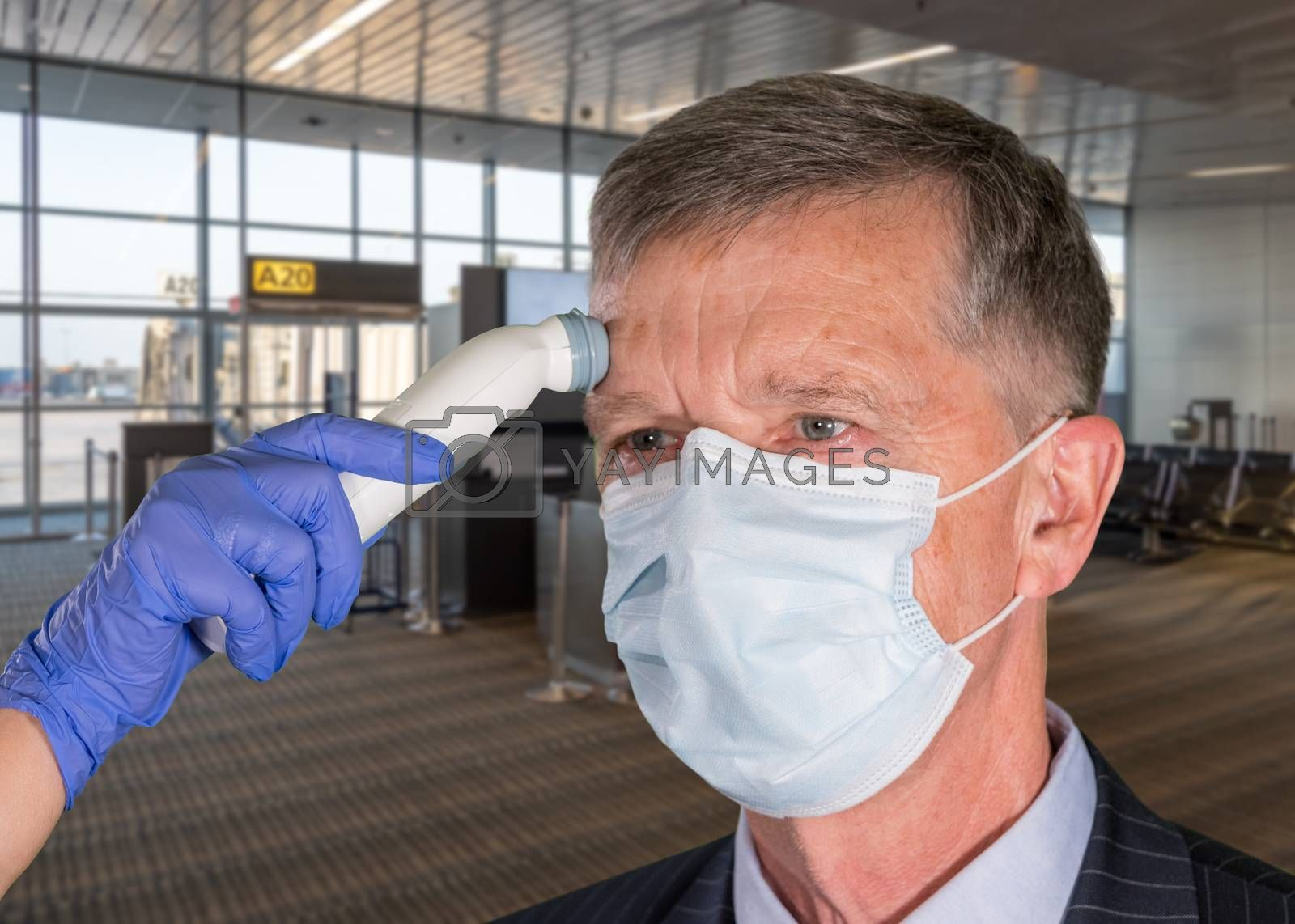 Mockup of airport terminal with senior adult wearing mask having a fever or temperature test taken to check coronavirus status