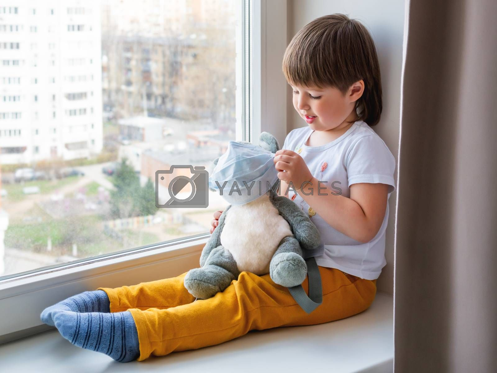 Toddler boy sits with koala bear in medical masks. Kid with plush toy look through window outside. Grey bear and child on home quarantine because of coronavirus COVID-19.