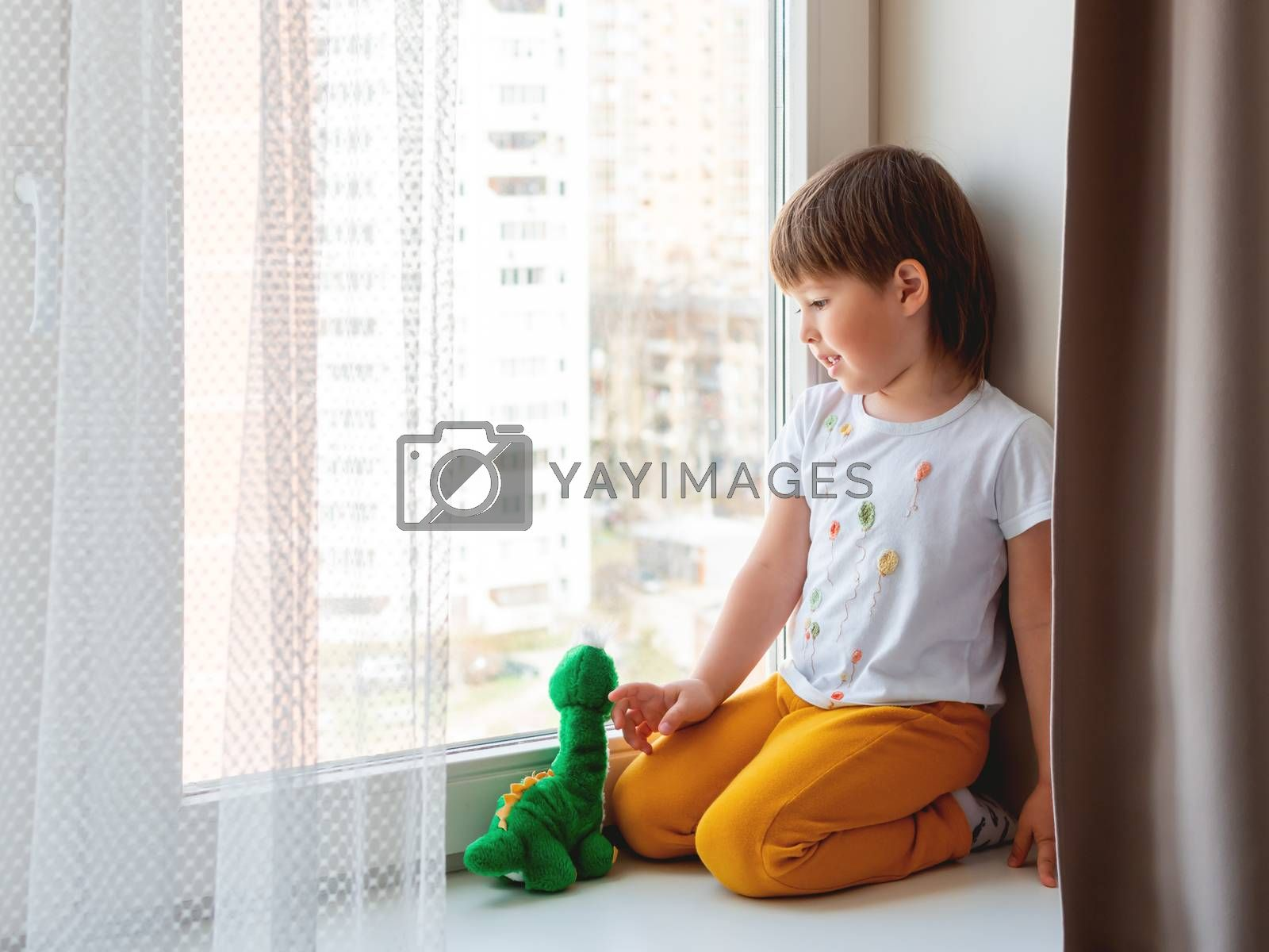 Toddler boy sits with green dragon or dinosaur. Kid with plush toy look through window outside. Child on home quarantine because of coronavirus COVID-19 waiting for somebody.