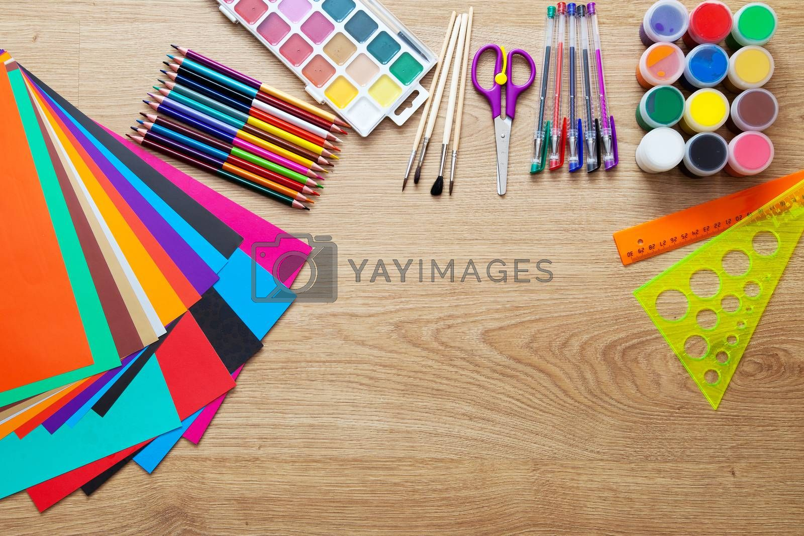 set of school supplies with pencils, paint, pens, paper, scissors and rulers on the floor