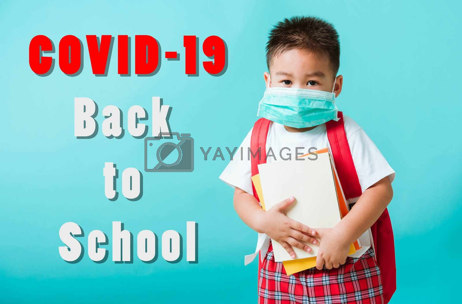 Back to school coronavirus Covid-19 education. Portrait Asian little child boy kindergarten wear face mask protective and school bag hold book before going to school, studio shot isolated background