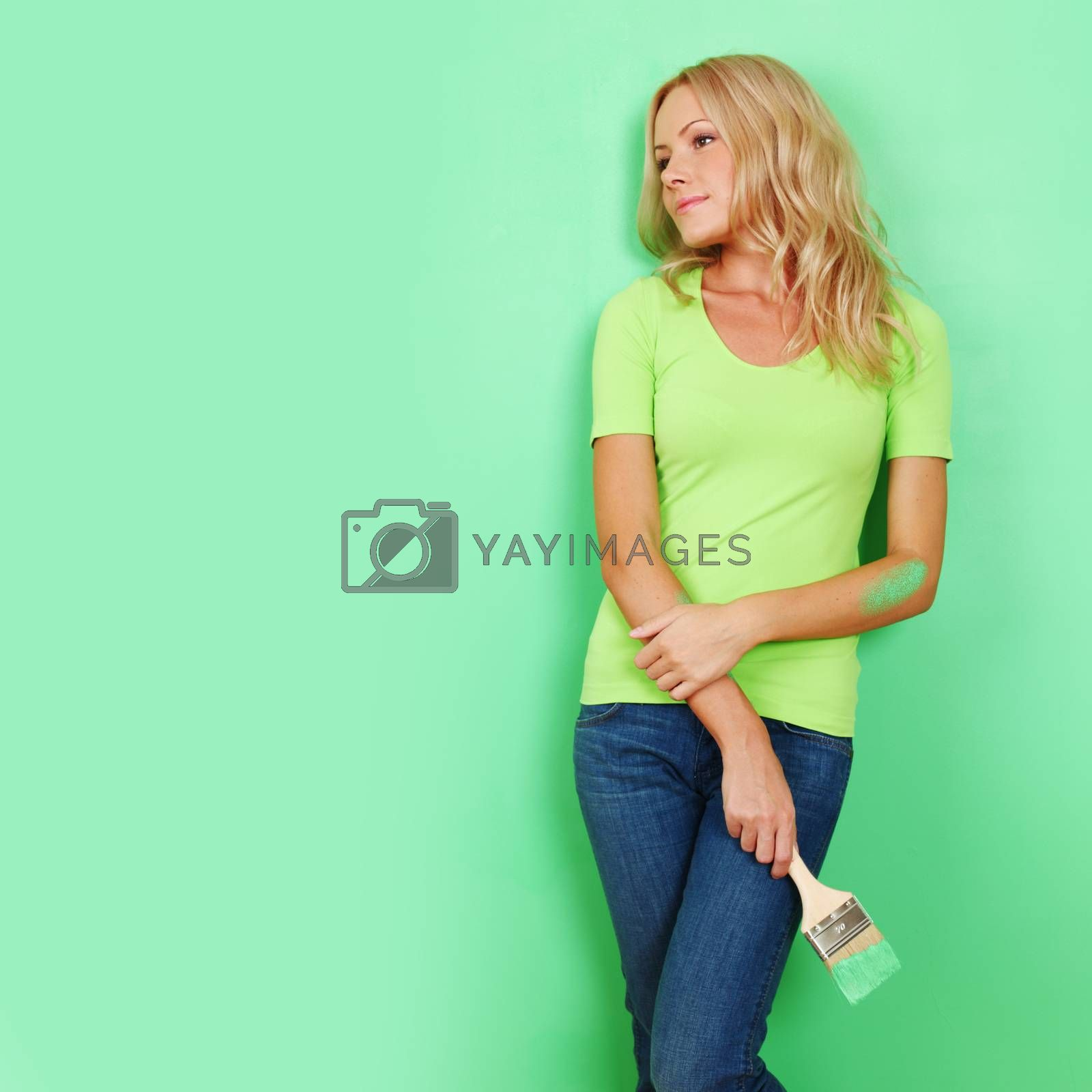 Young attractive woman with paint brush near fresh painted wall finished renovation copy space for text