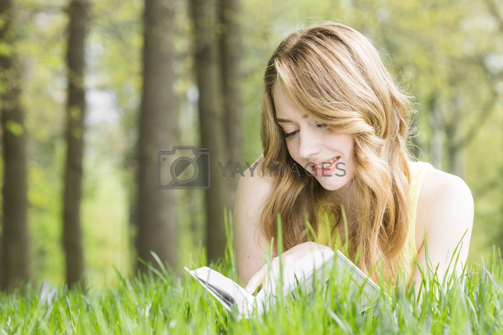 Young beautiful woman lays on green grass field and reads book, spring exam concept, copy space for text