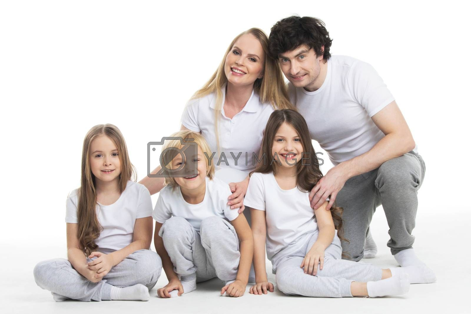 Happy smiling family of two parents and three children sitting on the floor studio isolated on white background