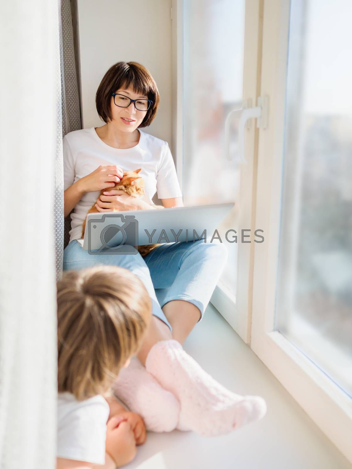 Woman in medical mask remote works from home. She sits on window sill with laptop and cute ginger cat on her knees. Lockdown quarantine because of coronavirus COVID19. Self isolation at home.