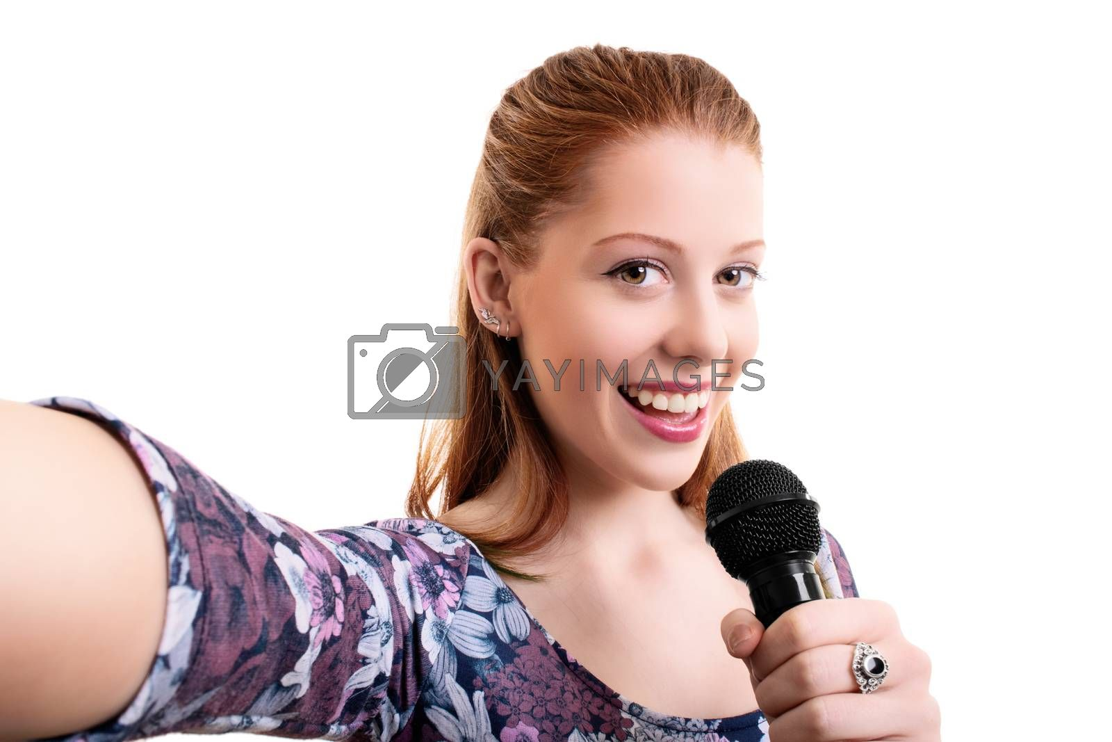 Beautiful young girl holding a microphone and taking a selfie, isolated on white background. Lifestyle, happiness, and social concept. Fashionable girl with a microphone singing and taking a selfie.