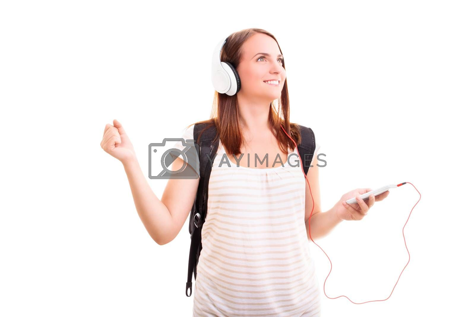 Beautiful smiling blond young girl with headphones listening to music, isolated on white background. Music and sound concept.