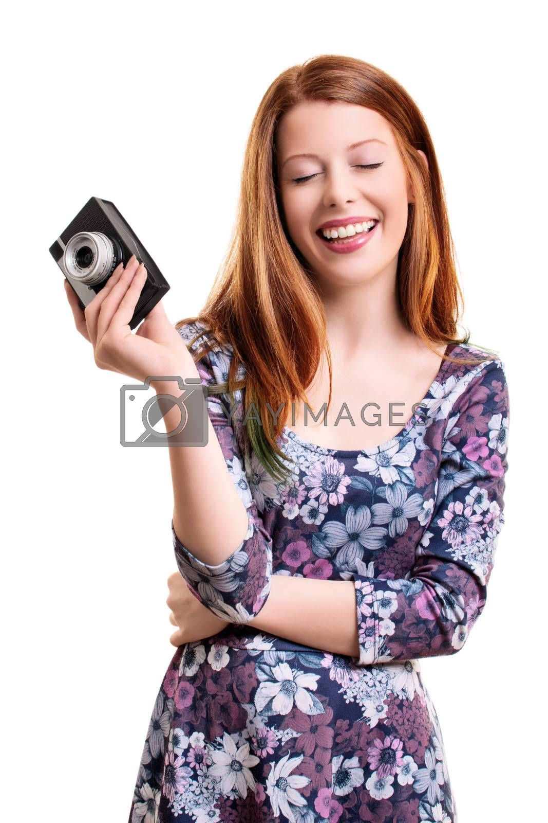 Beautiful smiling young girl with closed eyes, looking pleased and happy, holding an old camera, isolated on white background.