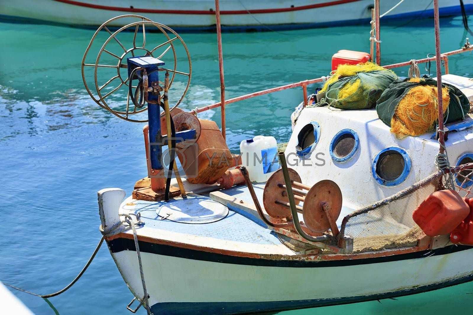 A fishing boat with fishing nets is anchored in the clear waters of the Ionian Sea. Loutraki, Corinth, Greece.