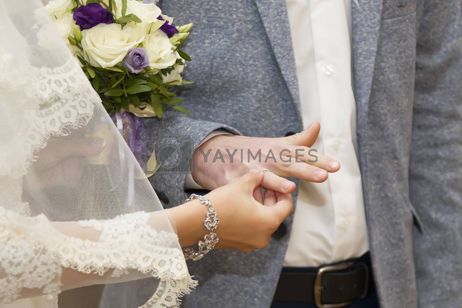 The groom wears an engagement ring to the groom. Dress the wedding ring