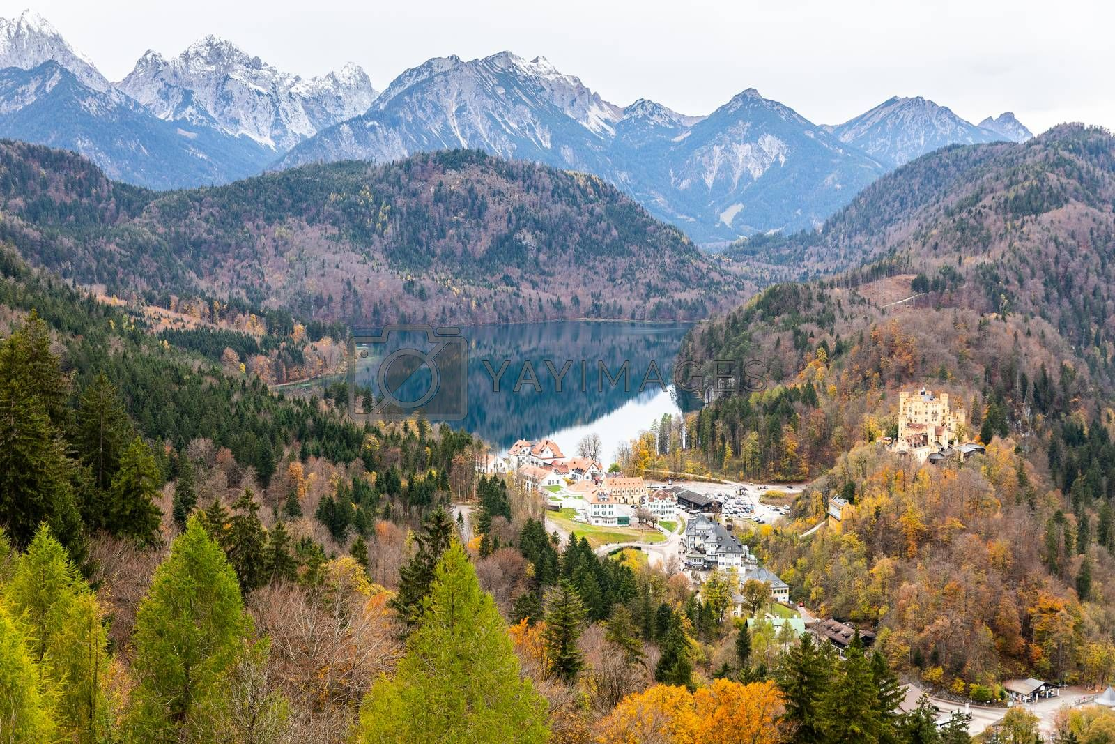 Aerial view over Alpsee lake and rural town surrounding by mountain range in autumn.