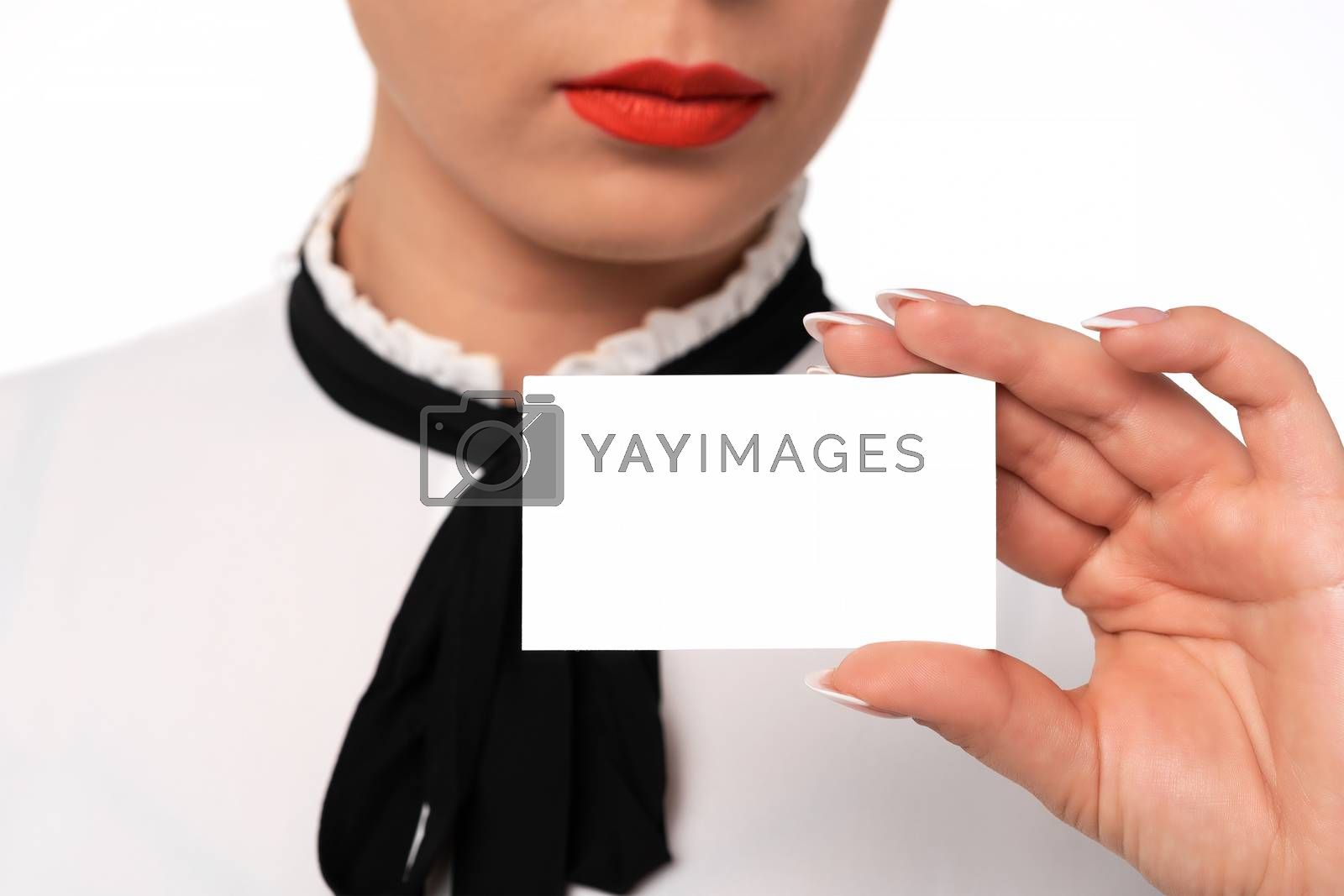 Young business woman with perfect fingernails holds blank business card in close-up.