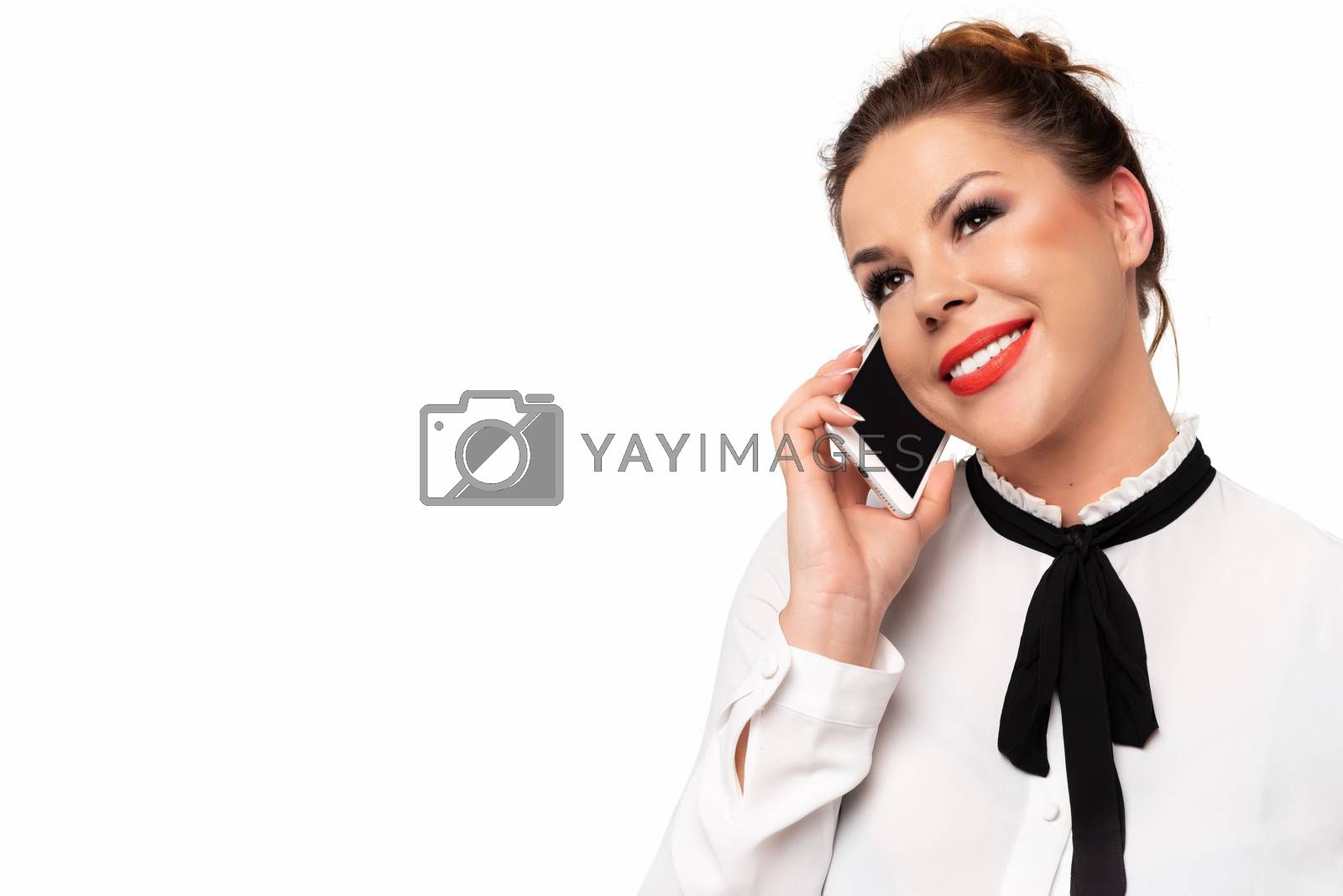 Portrait of beautiful young business woman talking on a mobile phone and smiling on a white background (copy space).