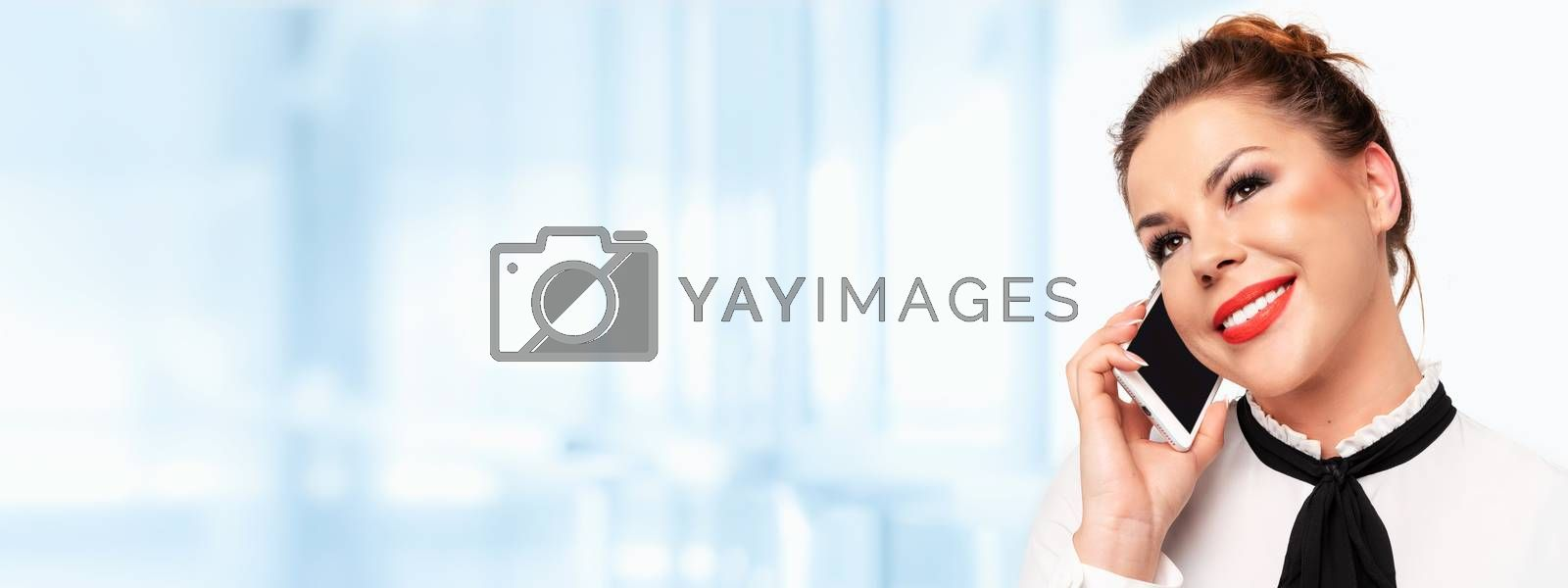 Modern communications banner -  beautiful young business woman talking on a mobile phone and smiling (copy space).